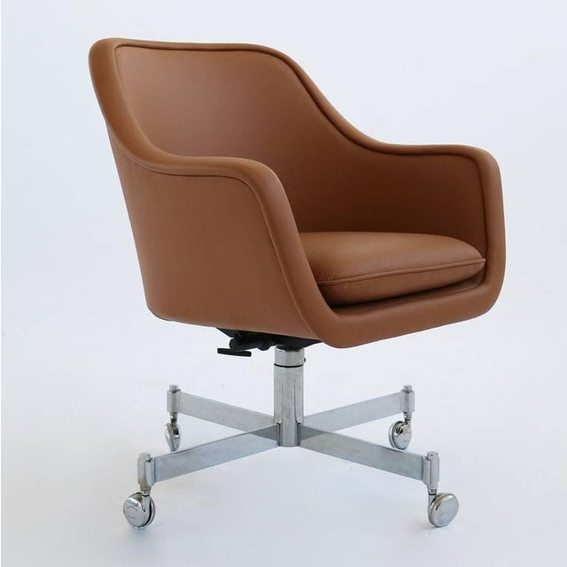 Desk chair by Ward Bennett. Reupholstered in a tan colored leather. The base, tilts, swivels, and has an adjustable...