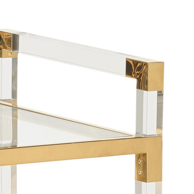 Clear acrylic with clear glass shelves and polished brass finished iron edging