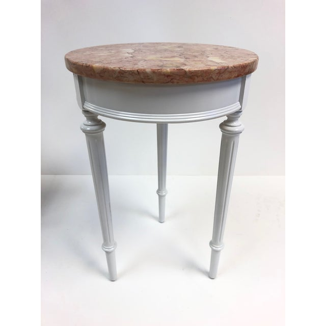 Pair of Hollywood Regency marble top side tables. White lacquered frames with round Italian marble tops.