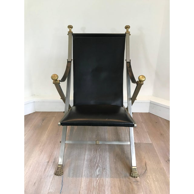 Pair of Maison Jansen campaign armchairs. Black leather seat with steel and brass accented frame. Wonderful patina to...
