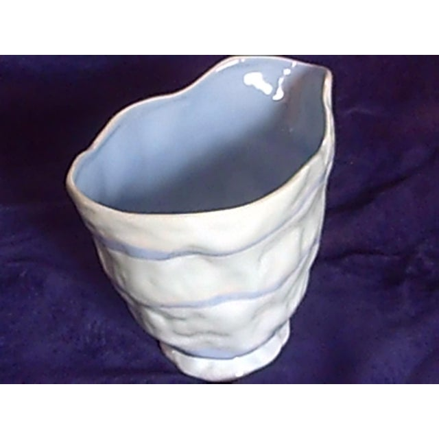 Looks like something out of Dr. Seuss. Lite blue glaze with a wavy stip coves this handmade ceramic vase. Bottom label...