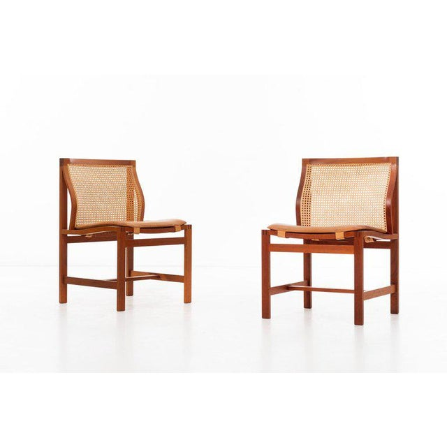 Rud Thygesen & Johnny Sorensen Set of eight curved-back dining chairs in teak and cane, with patinated leather seat...