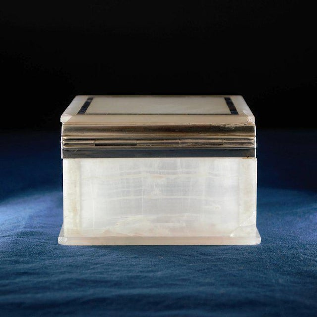 An elegant box made of white onyx with an inlay of lapis trimmed with a sterling silver hinged closure. Made by George...