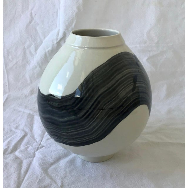 This small round porcelain vessel was inspired by the Korean Moon Jar. It is decorated with calligraphic strokes and...