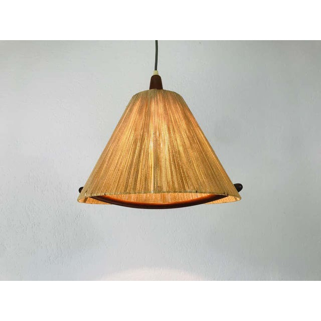 A wonderful Scandinavian teak hanging lamp made in the 1960s. It is fascinating with its rare lamp shade. Measurements:...