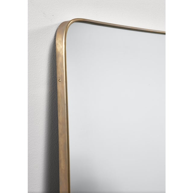 An overmantle, hallway or bathroom mirror with a simple and elegant original 1950s brass frame. The brass is in an...