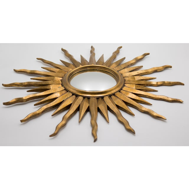 A beautifully carved Mid-Century French giltwood sunburst mirror with the original convex glass. This large starburst...