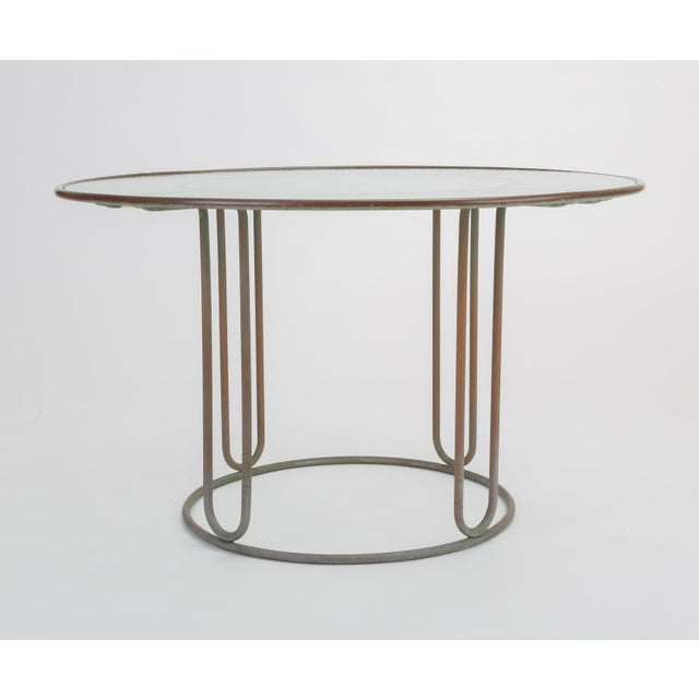 A patio dining table in patinated bronze designed by Walter Lamb and produced by Brown Jordan. The round frame is...