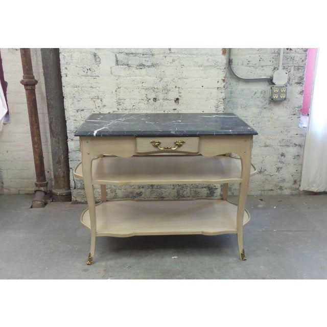 The Astor model Louis XV style night table having 3 drawers above 2 shaped shelves with raised edge molding and shown with...