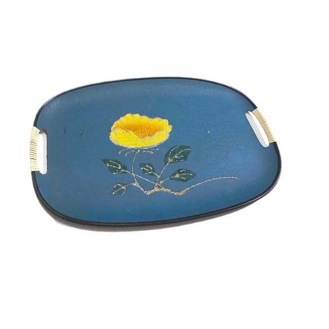 A funky turquoise tray with a yellow flower and a gold sparkly stem and sparkly green leaves. The front is in great...