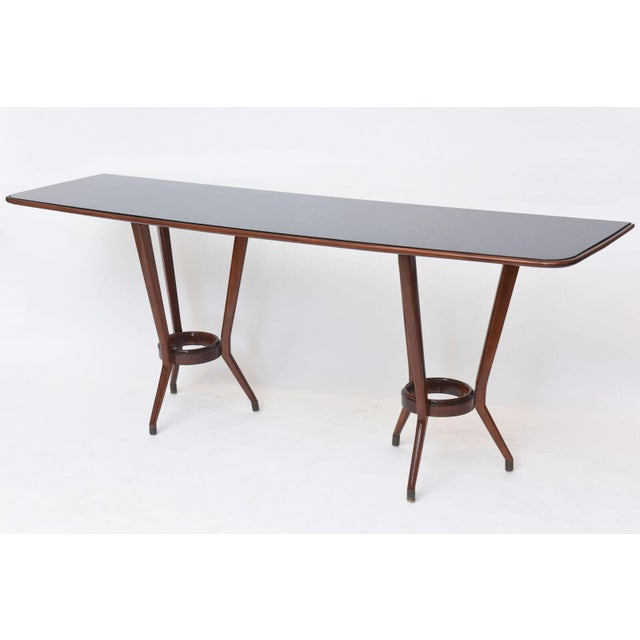 The inset black glass rectangular top with rounded edges with wood trim above two tripartite base supports joined by a...