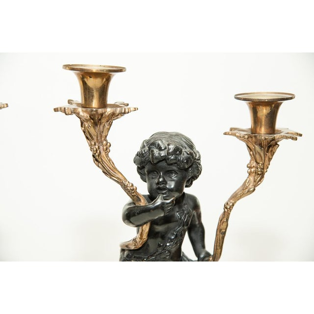 Pair of marble and bronze putti candelabra with gilt bronze accents and fluted marble base.