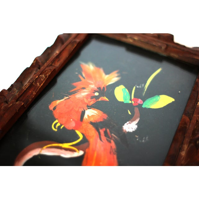 Feathercraft art depicting a red tropical bird with plumage resting on a branch. Framed in a hand-carved cedar frame under...