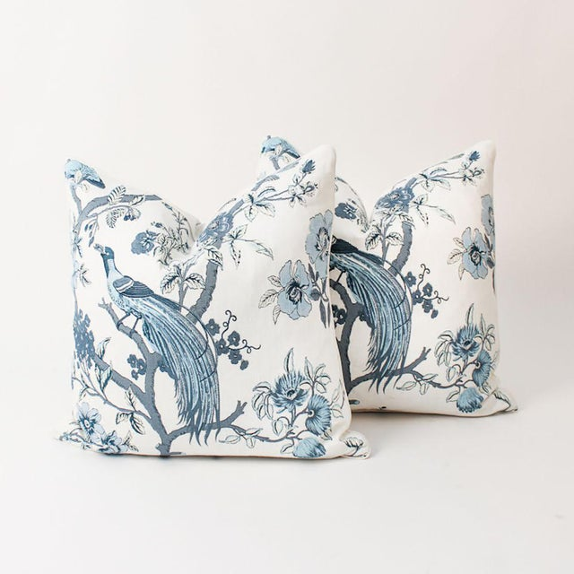 Pair of custom pillows made from a blue and ivory chinoiserie bird pattern fabric. Patterns on fronts, solid coordinating...