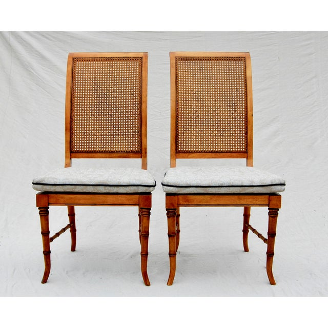 A pair of faux-bamboo chairs with lithe, graceful saber legs and original caning in excellent vintage condition. Custom,...