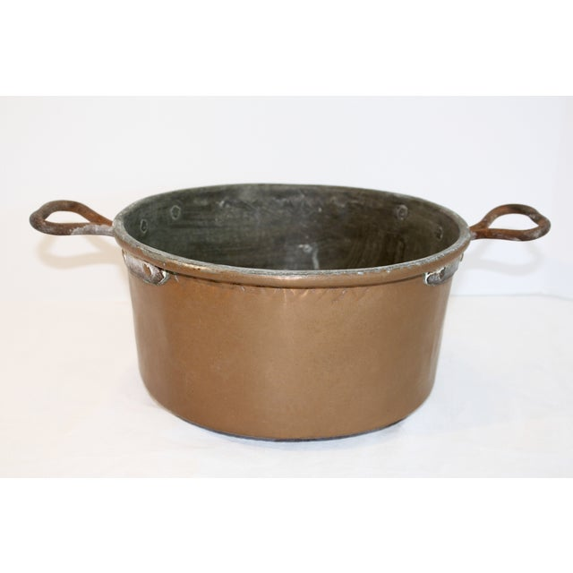 Offered is a rustic copper pot with hand-wrought handles and star pattern on the underside. Age related tarnish and wear.