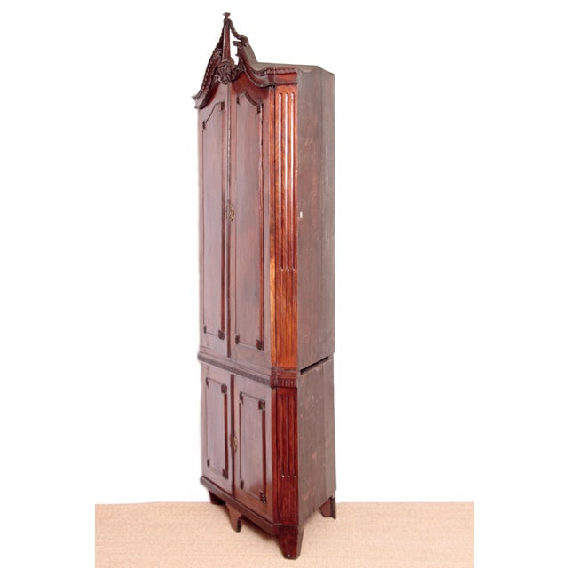 An 18th century Continental corner cabinet of mahogany in the English taste with split pediment at top with dentil...