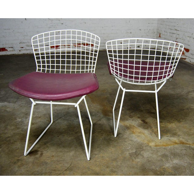 Classic mid-century modern white wire Bertoia side chairs with purple seat cushions. Buy one or all. Priced per chair....