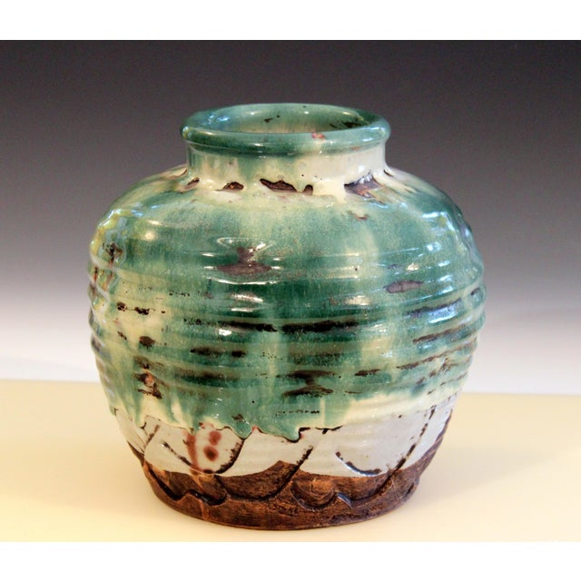 Awaji Pottery jar with dents and slashes covered in layers of thick lava glaze, circa 1930. Impressed export mark....