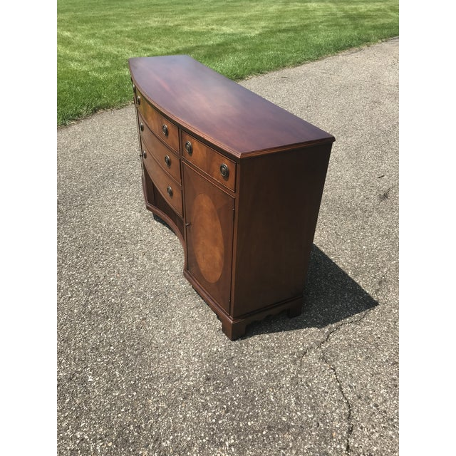 Curved front. Multiple wood species. Tambour doors on bottom middle. Side doors for storage. 3 large center drawers and...