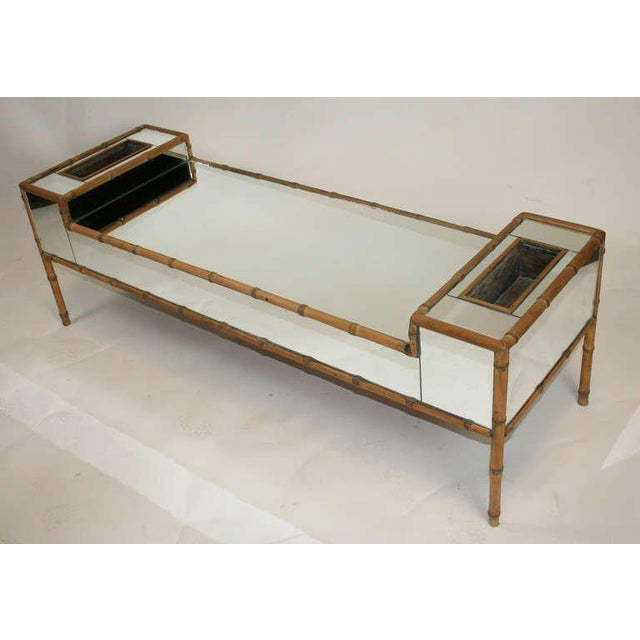 Chic coffee table covered in mirror and framed in faux bamboo trim. Upturned ends with planter pockets.