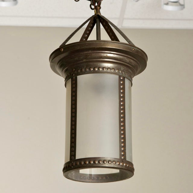 Early 20th century cylindrical frosted glass hall lantern features a beaded bronze frame and ceiling mount, c.1910....