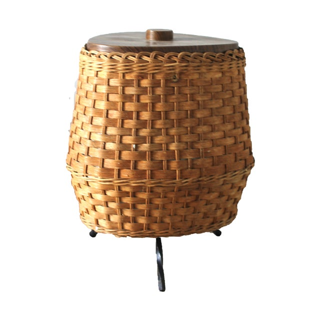 1960s wicker ice bucket with faux wood top and plastic lined interior. Stands on 3 iron legs.