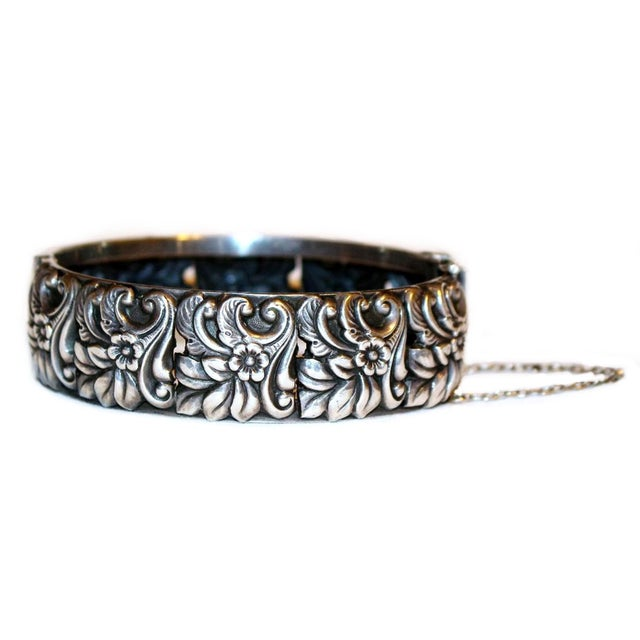 """Hallmarked sterling silver hinged bangle with a repoussé floral motif all around the exterior. The interior measures 7.25""""..."""