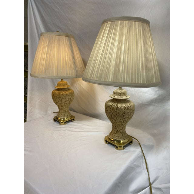 This is an adorable pair of petite cinnabar lamps in white. Cloth shade Shade base 12in and top of shade is 7in across....