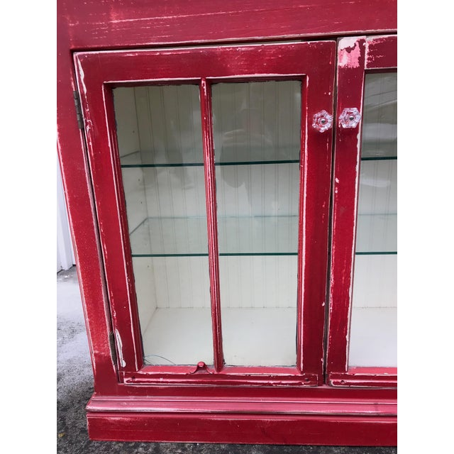 Beautiful rustic red cabinet with glass paneling, knobs, shelves. Solid construction, adjustable and removable glass shelves.
