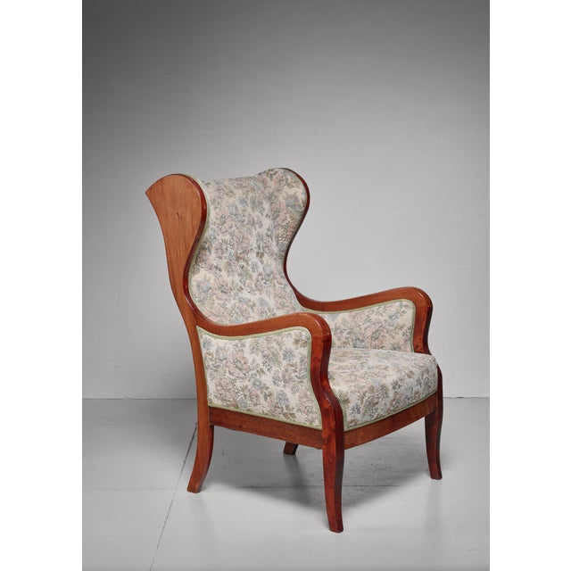 An elegant and comfortable mahogany wingback lounge chair with original floral fabric upholstery, by Frits Henningsen. The...
