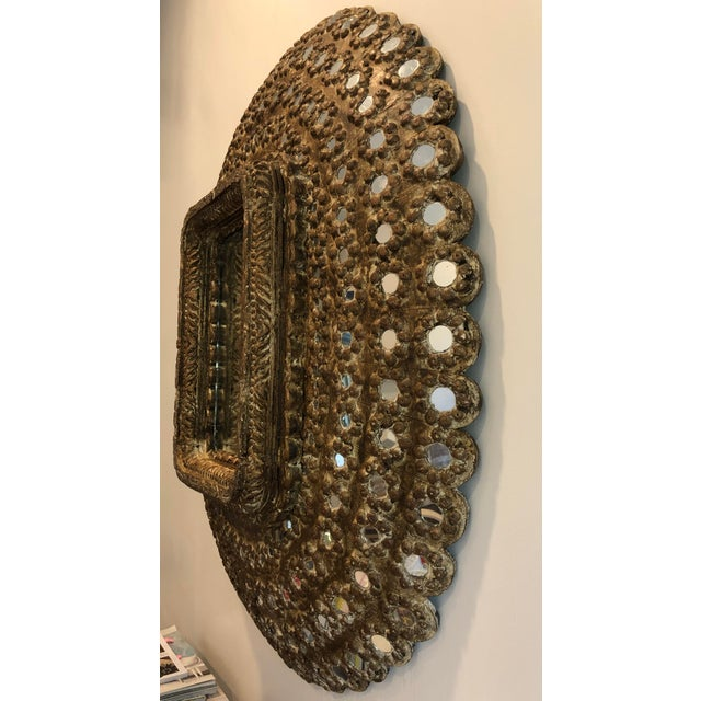This Moroccan Studded Wall Mirror was carefully hand-carved and inset with tiny mirrors. It's protruding oval shape allows...