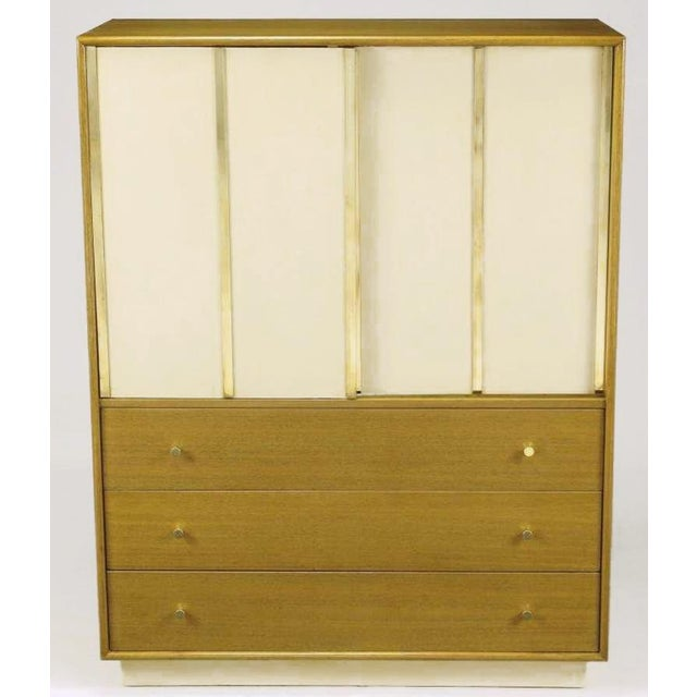 Harvey Probber bleached mahogany tall dresser or gentleman's chest, with ivory leather-clad sliding doors that feature...