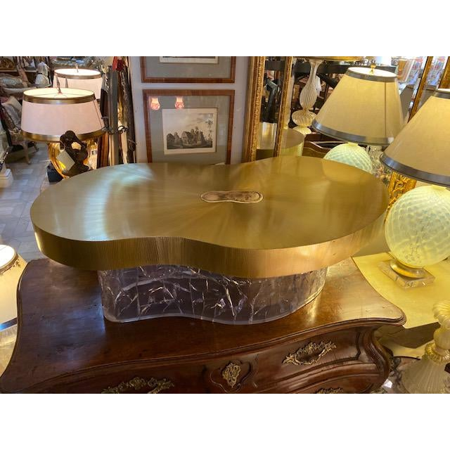 Very unique acrylic and brass curved coffee table. Made in the 1970s.