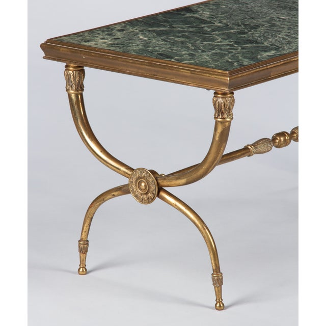 A handsome mid-century curule brass and green marble coffee table attributed to Raymond Subes, French circa 1940. The rich...