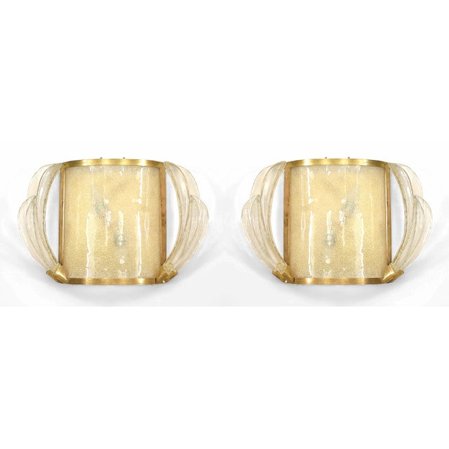 Pair of French 1940s brass framed wall sconces with Murano style clear glass double feather design sides with a textured...