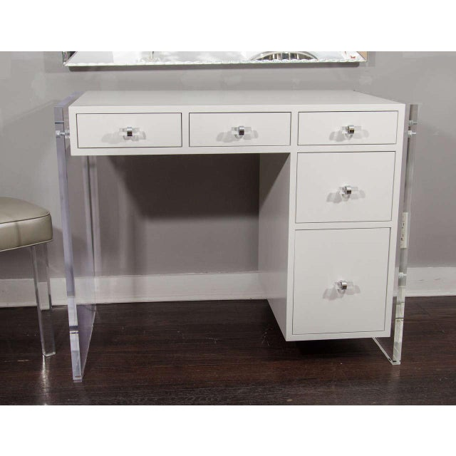 Custom white lacquer desk with Lucite side panels. Interior drawers are spray lacquered white. Hardware is chrome and Lucite.