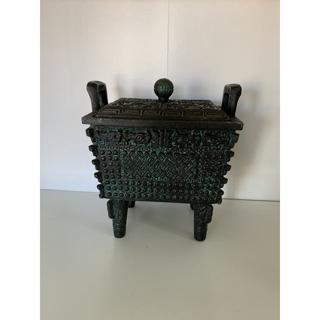 Interesting metal box on legs with intricate details. Interior features a mint green plastic liner. Excellent conversation...