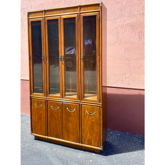Stunning Drexel Accolade China cabinet. Done in a Campaign style with gorgeous brass hardware. Tall and slender with a...