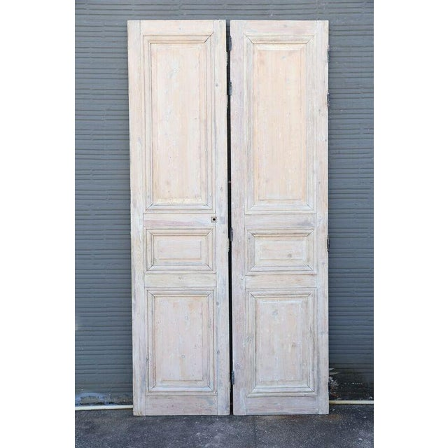 Louis XVI pine doors, sold as a pair. Original paint is stripped. Each door measures 26.25 inches wide and overall width...