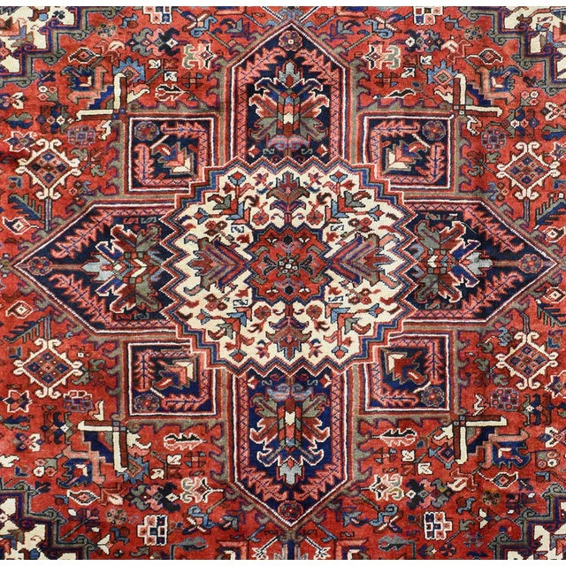 This beautiful rug is hand made, made in Iran. It features a pattern in a vibrant combination of red, navy , blue, white....