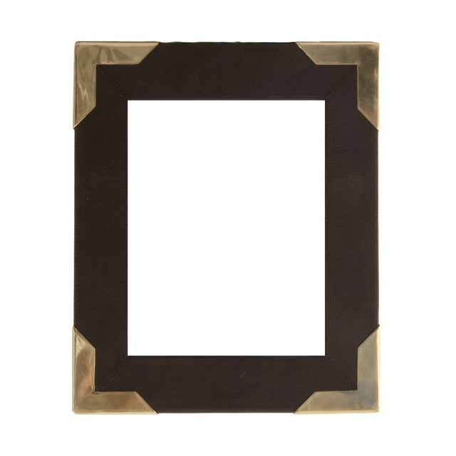 A striking Campaign-style picture frame, made of leather with brass corner details. This frame is new and therefore in...