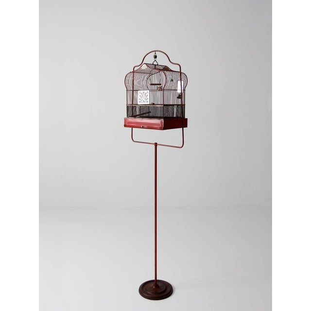 This antique bird cage was crafted by Crown. The red metal cage features a matching stand. The cage is a classic Crown...