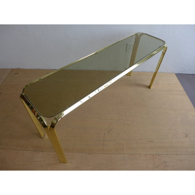 This a great console table in the style of Milo Baughman. The brass frame supports a smoked glass table top. Great vintage...