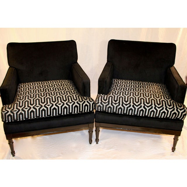 A pair of chic ebonized vintage 1950s club chairs. These chairs arrived in plastic that they had been covered in their...