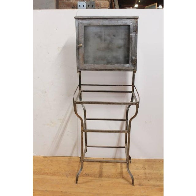 Antique American medical metal cabinet with glass shelves.