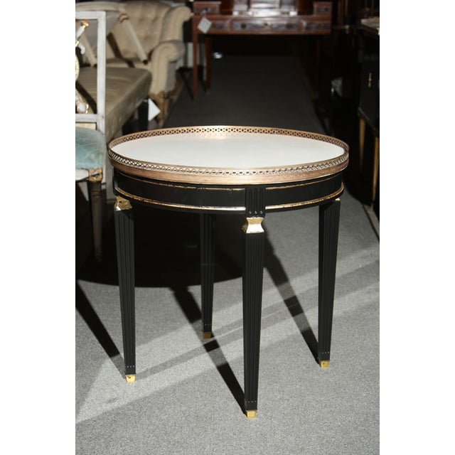 A lovely French gueridon table, circa 1940s stamped Jansen. The circular white marble top with brass gallery surround,...
