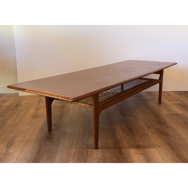 Long, low profile Danish MCM coffee table in good vintage condition. The wood surface is in good shape with a few cracks...