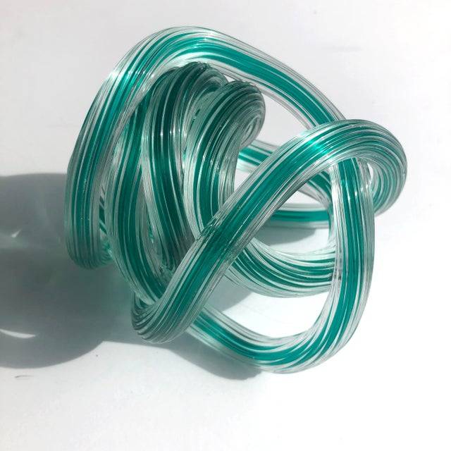 Fantastic vintage Italian glass knot sculpture in the style of Licio Zanetti. Clear textured glass with an emerald green...
