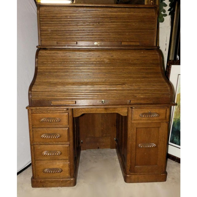 A fantastic vintage oak double roll-front desk. Features large work area with a variety of storage drawers and cubicles,...